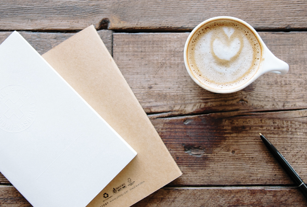 Latte and haiku journals on a wood desk or table top.