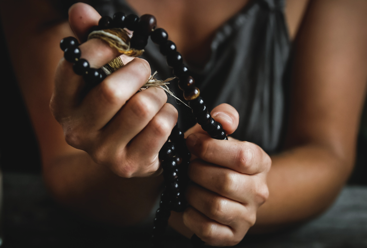 A woman's hands gripping a rosary.